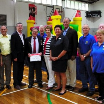 Lions club members with Community and YMCA members in front of Jumping Castle