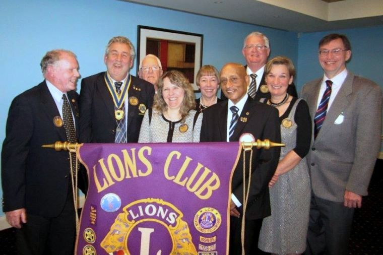 Women and men standing behind a lions club banner
