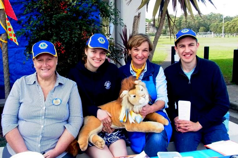 Women and young man wearing Lions caps at information table